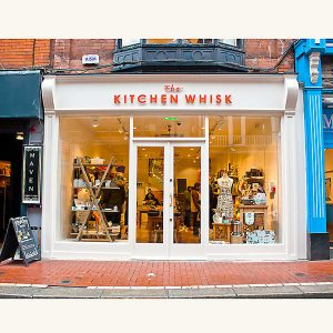 Image of a traditional wooden shop front from the front with the doors closed- The kitchen whisk store in Wicklow Street, Dublin 2