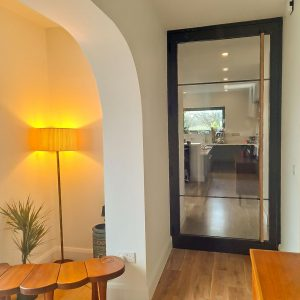 Glass Crittall Style Door in a house interior with ash handles