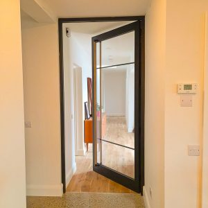 An open Crittall Style Door in Timber and Glass with ash handle in a modern home self build